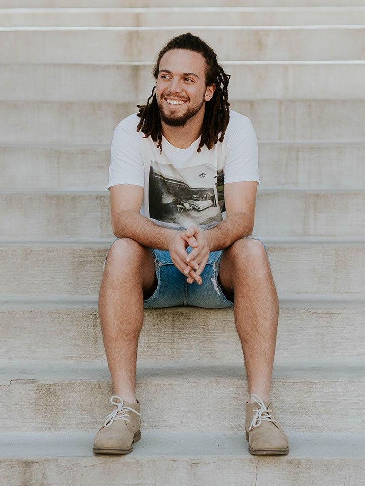 Young man smiling and sitting on some steps